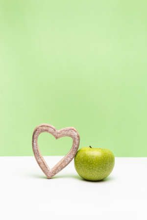 Apple and heart on vertical green and white background