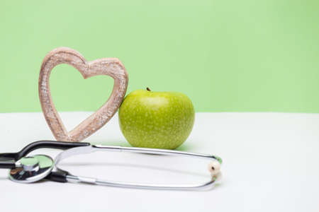 Apple, heart and stethoscope on horizontal green and white background