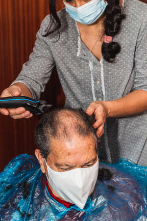 Daughter cutting her father's hair at home, vertical