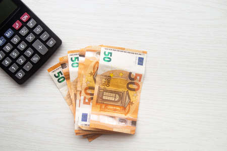 Euro cash banknotes and calculator on white table