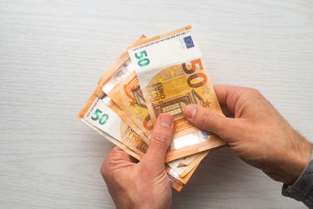 Man hands counting euro cash money banknotes on white table