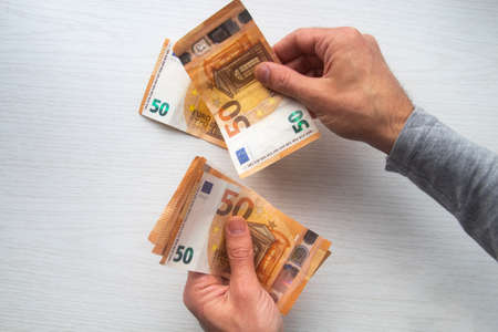 Man hands counting euro cash money banknotes on table