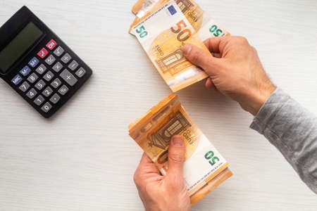 Man hands counting euro cash money banknotes and calculator on white table