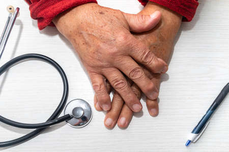 Hand of elderly man with osteoarthritis at doctor's office on white table Stock fotó