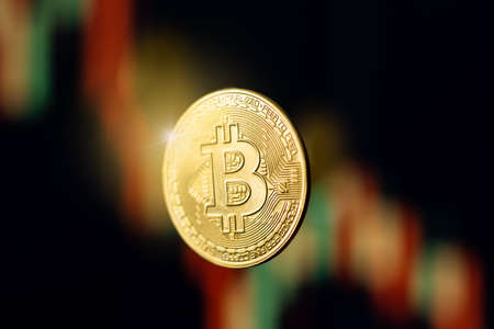 Bitcoin coin with light flare on defocused stock price graph