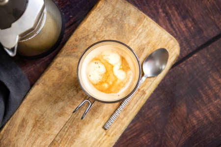 Cup of coffee with milk and teaspoon on wooden table and Italian coffee pot. Top view