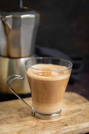 Cup of coffee with milk on wooden table and Italian coffee pot in the background. Vertical
