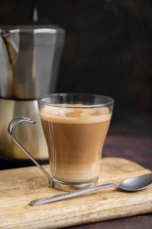 Cup of coffee with milk and teaspoon on wooden table and Italian coffee pot in the background. Vertical