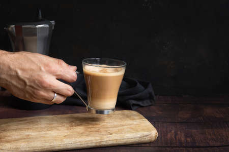 Man's hand holding cup of coffee with milk on wooden table and Italian coffee pot in the background Stock fotó