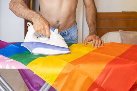 Unrecognizable young man shirtless ironing lgbt flag on ironing board Stock fotó