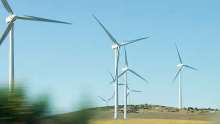 Wind generators spinning in operation viewed from a moving car Stock fotó