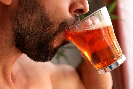 Caucasian man with beard drinking red tea by the window Stock fotó