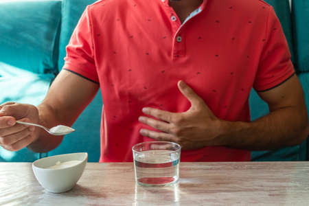 Caucasian man with stomach ache preparing fruit salt