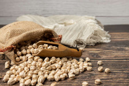 Sack of chickpeas on wooden table. Close up