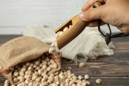 Hand pouring chickpeas into sack on wooden table