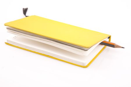yellow notebook and pencil on  white background photo