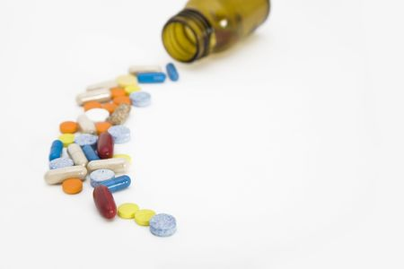a colorful stream of pills coming from a pill bottle - on a white background Stock Photo
