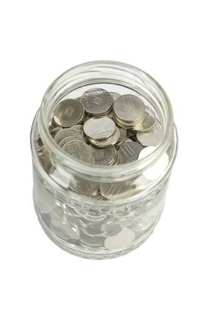 glass jar with silver coins on white background photo