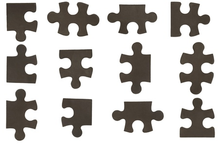 different black puzzle pieces over white background photo