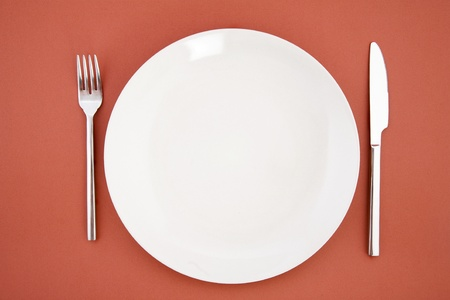 top view of white plate, fork and knife, restaurant tableware photo