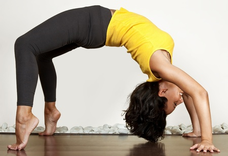 pretty girl arching her back like a bridge, gym exercise photo