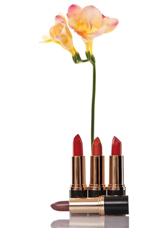 glamor red shiny lipstick and yellow flower on white background photo