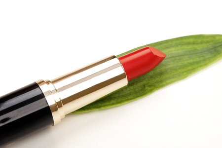 glamor red shiny lipstick and green leaf isolated on white background photo