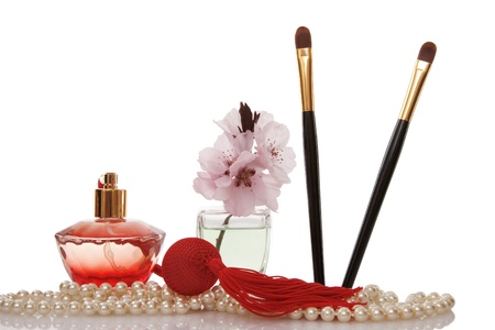 Pearls beads, perfume, two cosmetics brush and cherry flower on white background photo