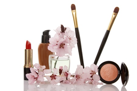 cosmetics and cherry flower on white background