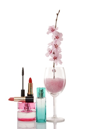 perfume bottles, lipsticks, cosmetics and cherry flower on white background photo