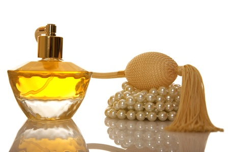 Perfume in a glass bottle and pearl beeds on white background photo