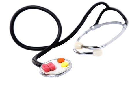 medical concept with colorful pills and stethoscope on white photo