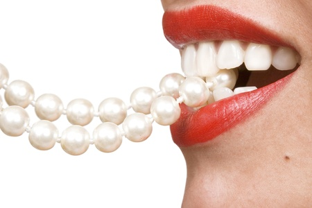 woman smiles showing white teeth, holding a pearly necklace in to the mouth, teeth care concept