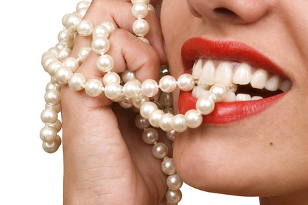 woman smiles showing white teeth, holding a pearly necklace in to the mouth, teeth care concept photo
