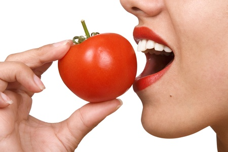 woman eat: Young Woman Eating Tomatoes. Portrait of smiling attractive young woman with ripe tomato, white background, freshness and healthy food concept