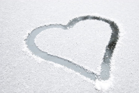 Heart shape drawn on white snow, love symbol for Valentine Day, selectiv focus Stock Photo - 9724998