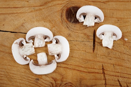 fresh champignon mushroom sliced on wooden background  photo