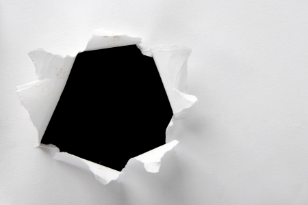 breaking through: Hole in the white paper with torn sides Stock Photo