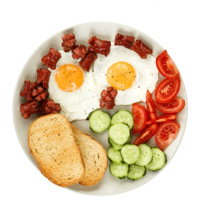 english breakfast: close-up of fried eggs with sausage and vegetables