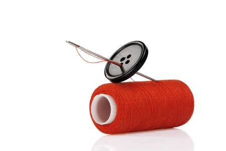 red spool, black button and needle isolated on white background