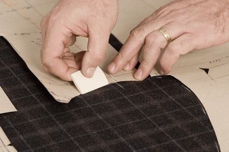 tailor measure: Tailor at work, drawing line on fabric with chalk Stock Photo