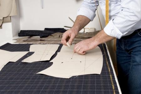 Krawiec w pracy, rysunek linii na tkaniny z kredą