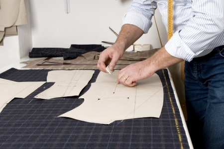 cloth manufacturing: Tailor at work, drawing line on fabric with chalk Stock Photo