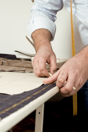 Tailor at work, drawing line on fabric with chalk photo