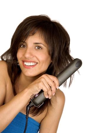 Portrait of beautiful woman using hair straighteners photo