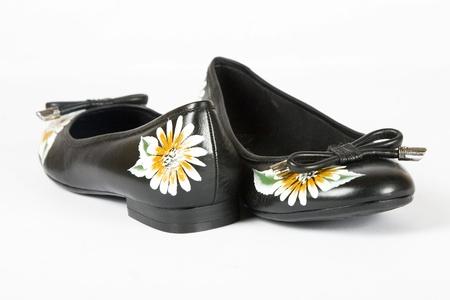 pies bailando: zapatos de mujer color negro con flores impresas sobre fondo blanco Foto de archivo