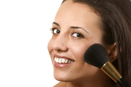 Portrait of attractive young woman applying blusher photo