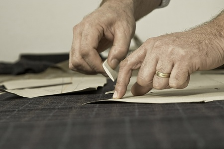 garment: Tailor at work, drawing line on fabric with chalk Stock Photo