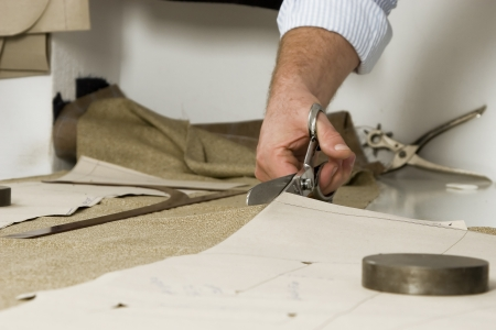 dressmaker: Tailor working at studio cutting fabric, detail of hand with scissors