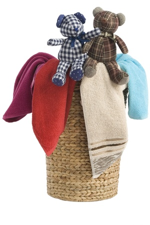 colorful towels in a basket isolated on white background and a resting teddy bears photo